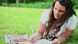 stock-footage-brunette-woman-writing-on-notebooks-in-a-park